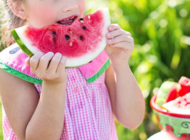 Girl eating a watermelon, giving the image of health